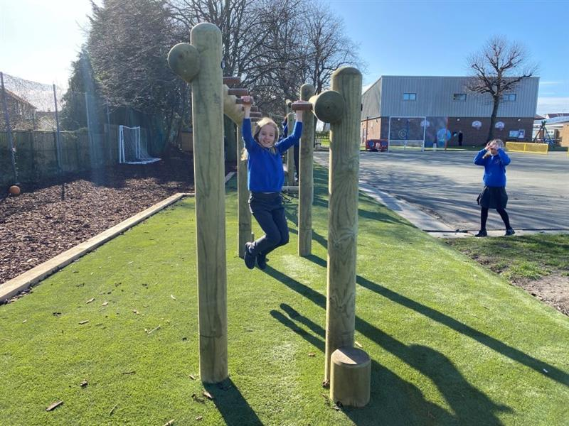 One girl with blonde hair wearing a blue school jumper climbing across the monkey bars at the end of the forest trim trail whilst one girl wearing a blue school jumper and a grey skirt stands at the side to watch. The trim trail has been installed next to the school playground.
