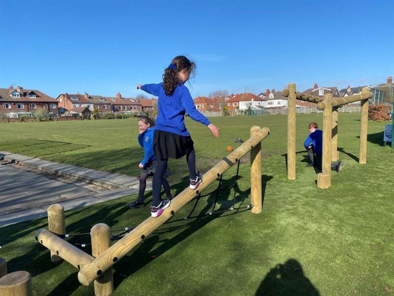 One girl wearing a blue school jumper and black skirt is crossing the twist net with incline beam whilst one boy finishes the trim trail at the monkey bars and one girl walks back to the start of the trail.