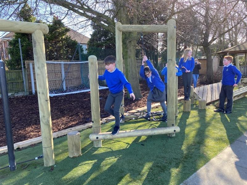 5 children wearing blue school jumpers crossing the stepping stones and triangular net landscape which has been installed onto artificial grass next to the forest area at the school.