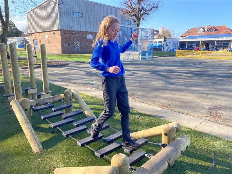 One girl with blonde hair wearing a blue school jumper and grey jeans is crossing the wobbly bridge that has been installed onto artificial grass. The wobbly bridge is part of the schools new forest trim trail.