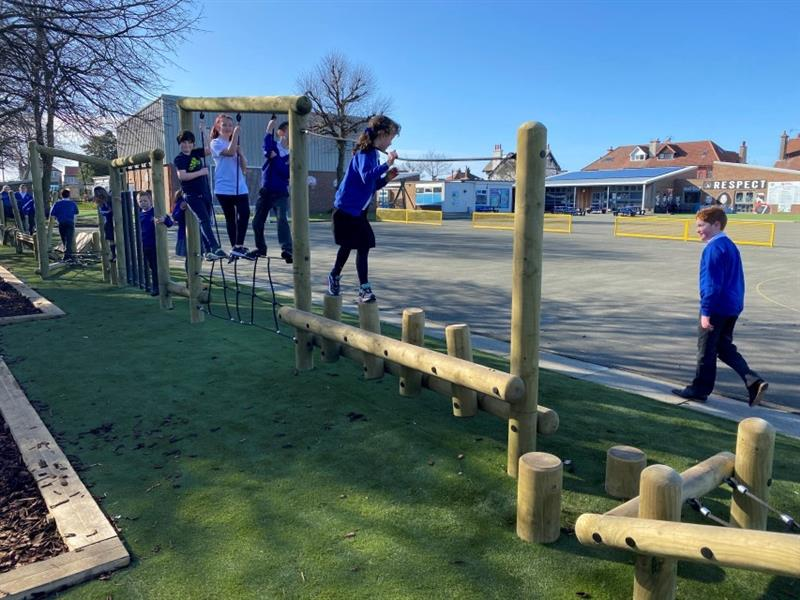 12 children playing on the forest trim trail that has been installed onto artificial grass in a straight line. Behind the trim trail is the school building and playground.