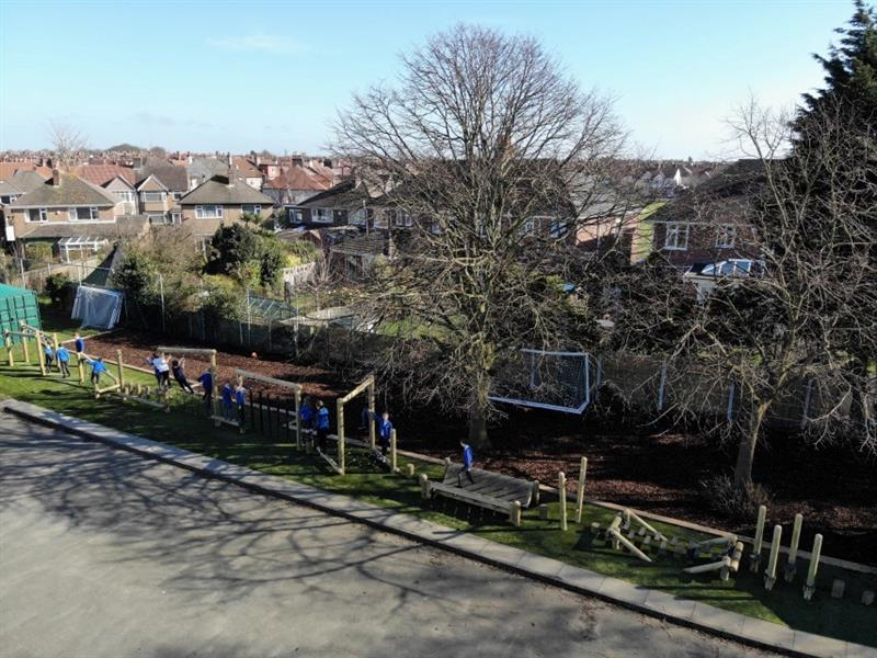 Aerial shot of children playing on the forest trim trail which has been installed onto the artificial grass next to the forest area of the school which includes two large trees.