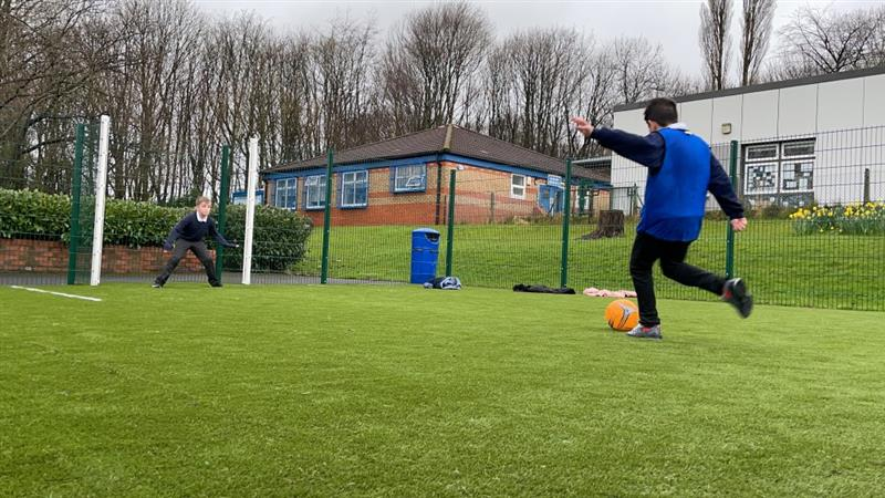 two boys playing football on a MUGA. one boy wearing school uniform and a blue vest kicking a bright orange football into a net whilst one boy wearing school uniform stands in the next to try and stop the ball from going in.