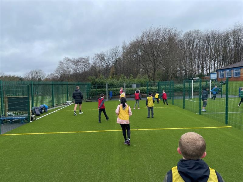 9 children playing football on a MUGA, 4 wearing yellow vests and 4 wearing red vests whilst one teacher wearing a black coat and black shorts supervises.