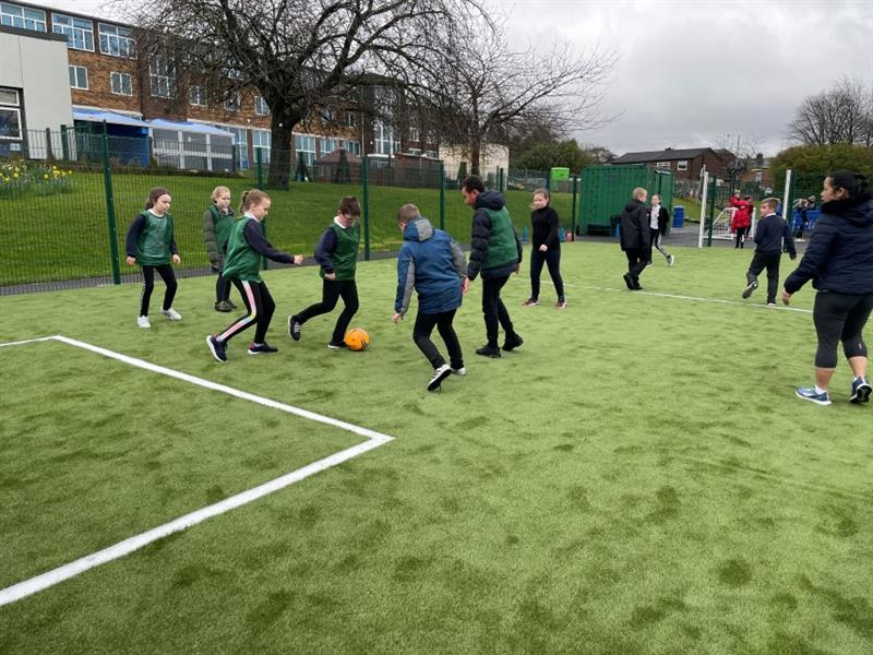 11 children playing football on a multi-use games area pitch, 4 children wearing green vests and the remaining children wearing their PE kit. One teacher stands on the pitch with the children to supervise.