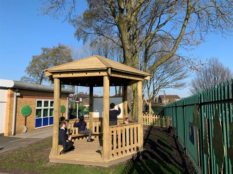 A 3.5m gazebo placed in front of a large tree with 4 children sat inside of the gazebo and 1 child writing on a whiteboard which is inside of the gazebo.