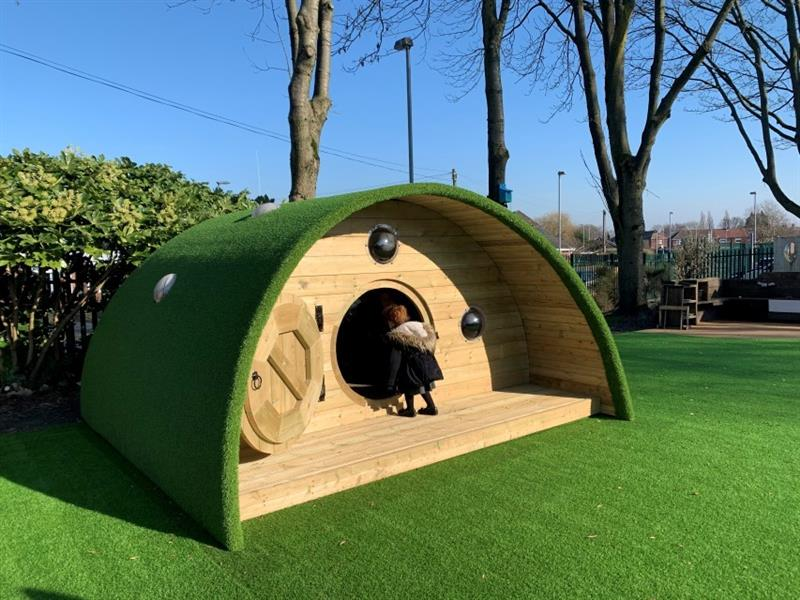 One KS1 child who is a girl, wearing a black coat with fur attached to the hood is at the entrance of a hobbit house looking inside of the house.