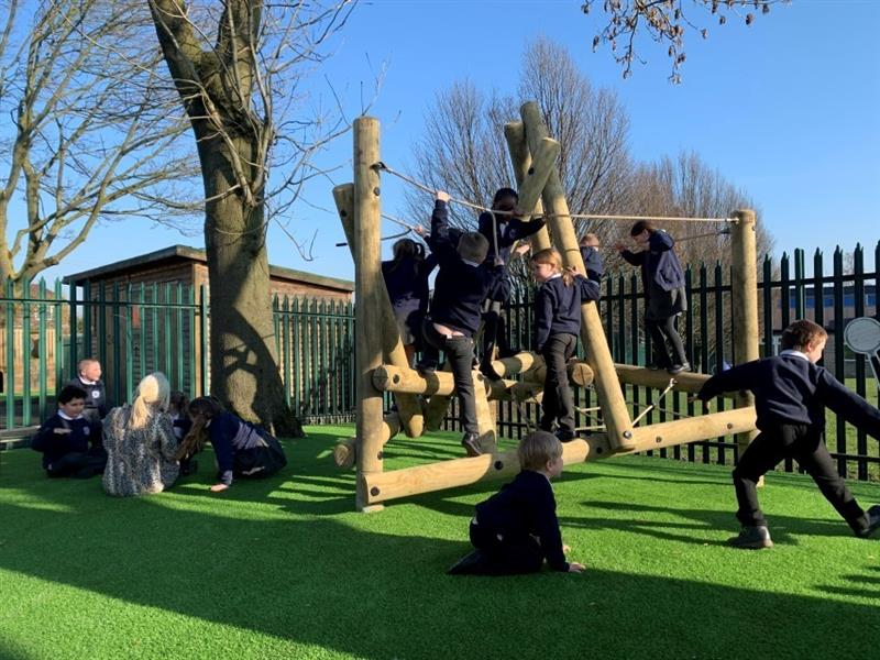 6 children playing on an open-ended climbing frame, with 2 children playing nearby and 4 children sat on the artificial grass near a tree with a teacher.
