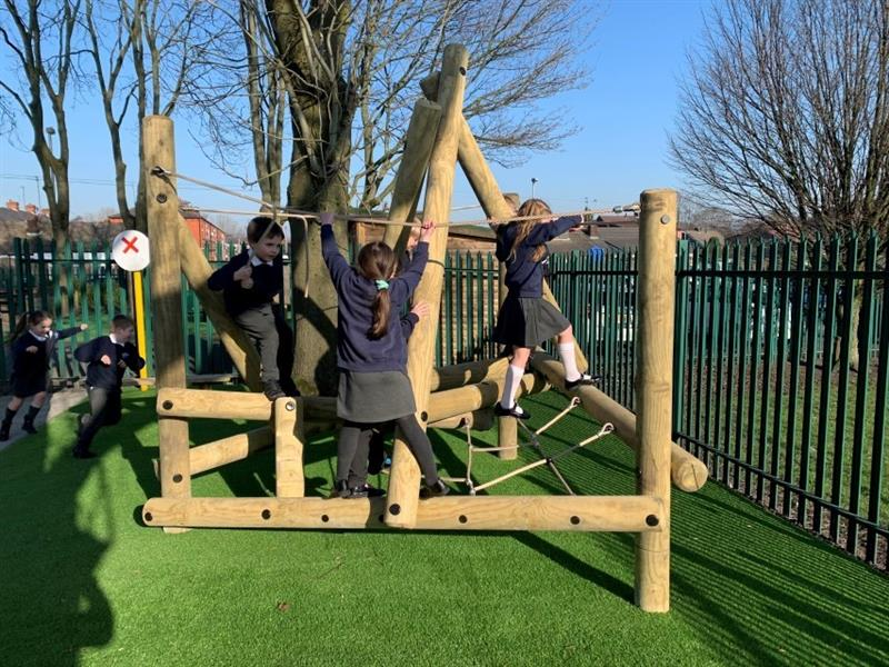 Three children playing on an open-ended climber installed onto artificial grass with two children running past the climbing frame.