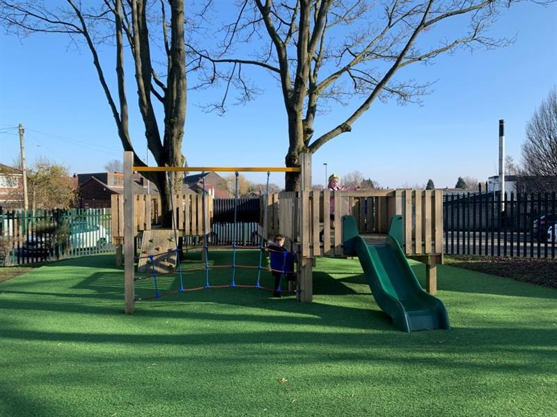 2 children, one boy and one girl playing on a bespoke treehouse with a green slide, installed onto artificial grass.