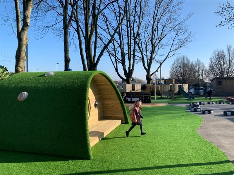 One girl wearing a pink coat walking out of the hobbit house onto the artificial grass with trees and blue sky behind the hobbit house.