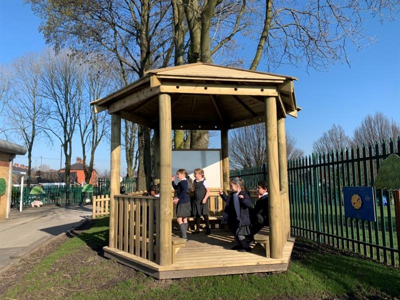 7 children inside a 3.5 hexagonal gazebo with a whiteboard, 2 of the children are stood near the whiteboard, 1 child is getting up off the bench. The gazebo has been installed next to a green fence.