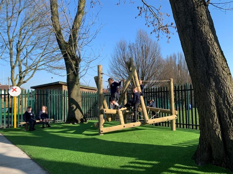 5 children playing on a play frame which has been installed onto artificial grass whilst two children, one boy and one girl sit nicely on a bench smiling at the camera.