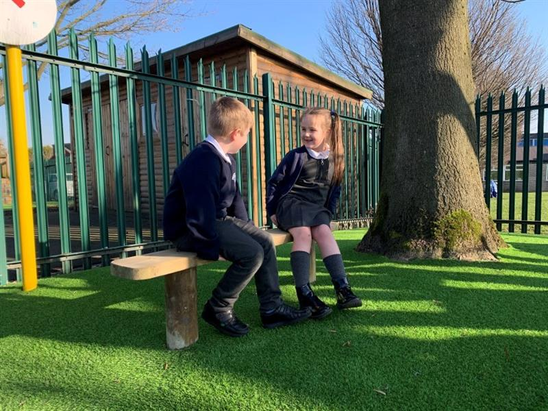2 children sat on a bench, one girl and one boy, smiling at each other whilst they enjoy the sunshine, the bench has been placed in front of a large tree.
