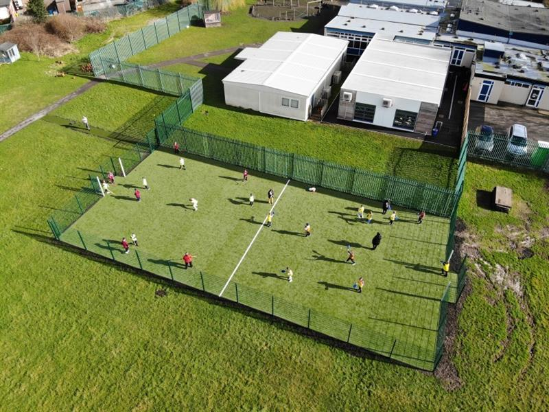 Primary school children playing hockey on MUGA which features a halfway line, artificial grass and 2m rebound fencing.