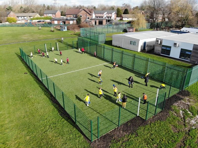 Primary school children playing hockey, one red team and one yellow team on a muga pitch.