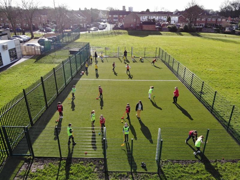 21 children having a hockey lesson from 4 teachers on MUGA pitch, wearing yellow, red and green coloured bibs.