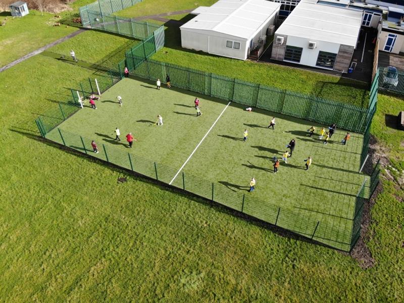 Primary school children wearing red, yellow and orange bibs having a hockey lesson on MUGA pitch, whilst 2 children sit in a recessed goal end resting.