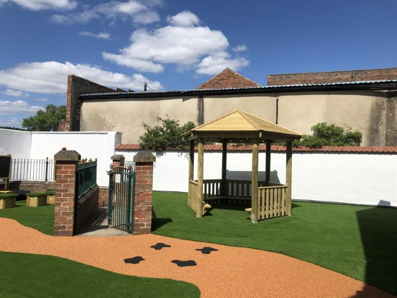 an outdoor gazebo on artificial grass and wet pour surfacing
