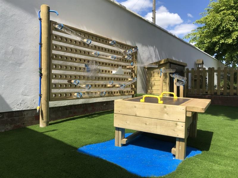 A Pentagon Play Water Wall alongside a water table on artificial grass