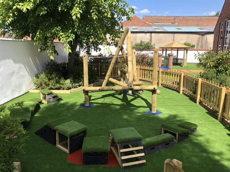 A Pentagon Play climbing frame on artificial grass surrounded by Get Set Go Blocks