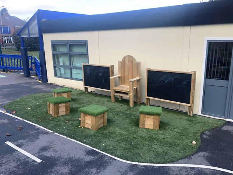 A storytelling chair and moveable seats installed onto artificial grass surfacing