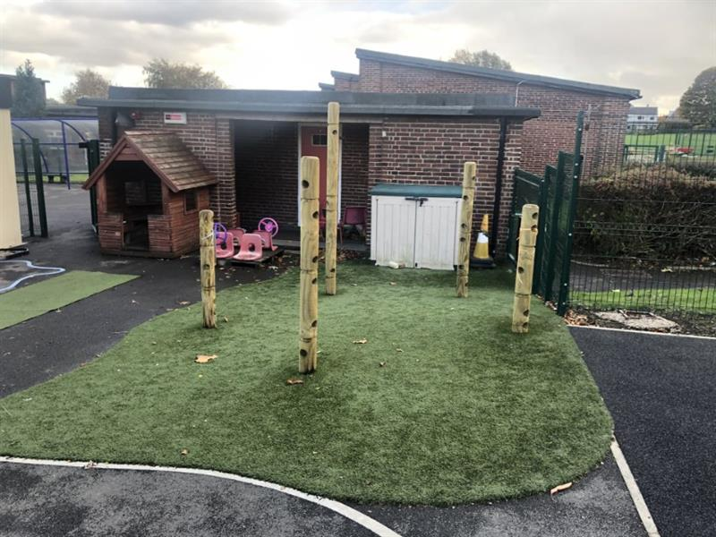 outdoor play equipment for eyfs installed onto artificial grass surfacing