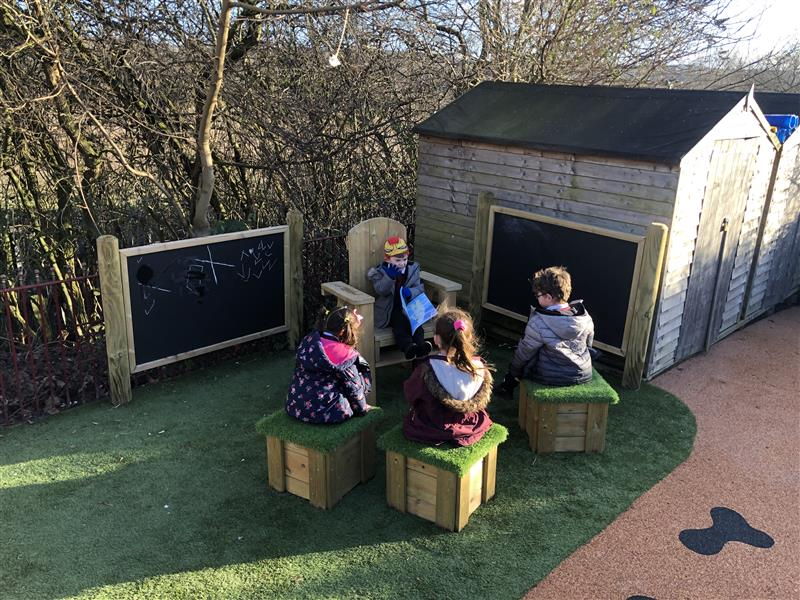 Four children reading around our Story Telling Chair