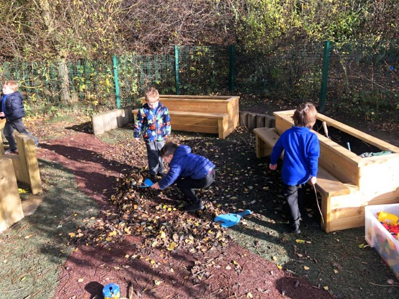 Children playing with leaves fallen on playbond surfacing