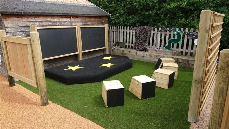 An inspirational eyfs outdoor area featuring drum seats, playground stage and surfacing