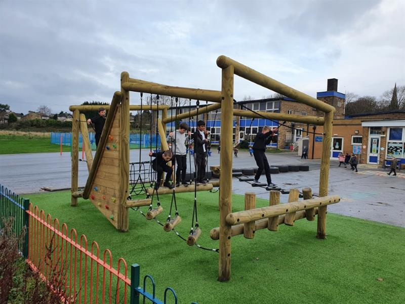 4 children swinging, climbing and balancing on Pentagon Play's Puzzlewood Forest Circuit installed on their school playground with artificial Grass underneath