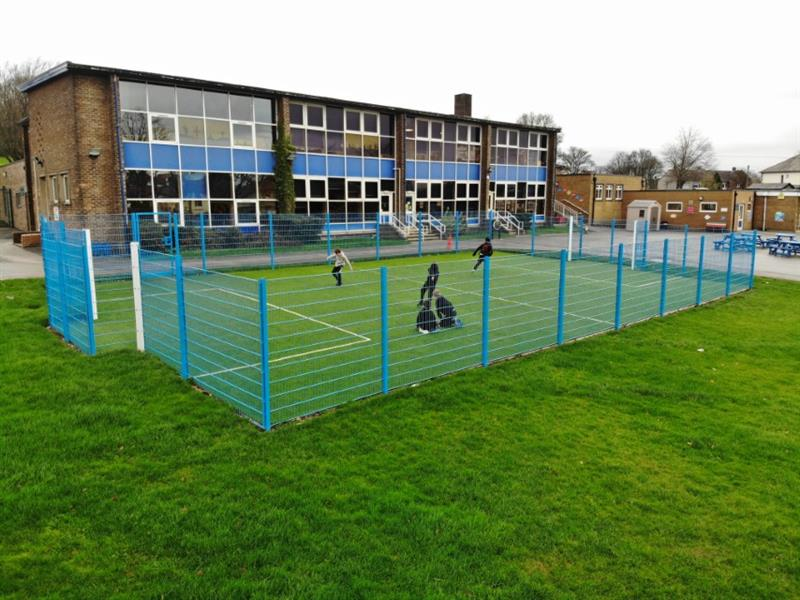 5 children playing football on a 20m x 12m muga pitch with blue sport fencing, recessed goal ends and bright green artificial grass