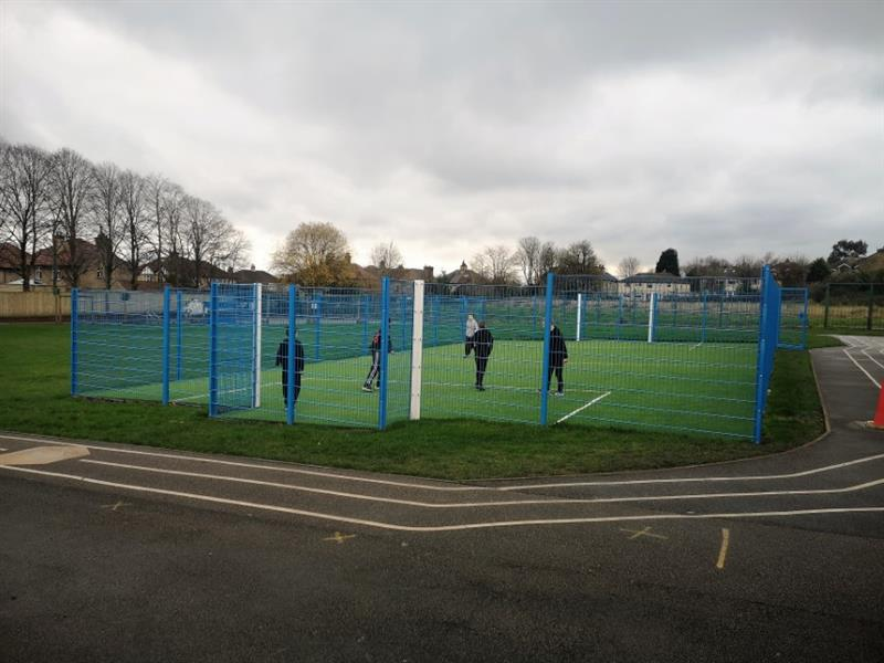 A 20m x 12m muga with blue sport fencing and artificial grass surfacing installed onto a school field with 5 children playing football