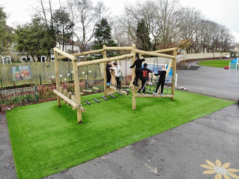 3 children playing on Pentagon Play's Puzzlewood Forest Circuit installed on the school playground with Artificial Grass underneath
