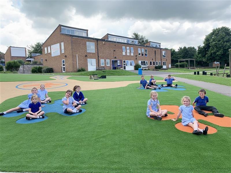 Children sitting on the grass area on their new playground
