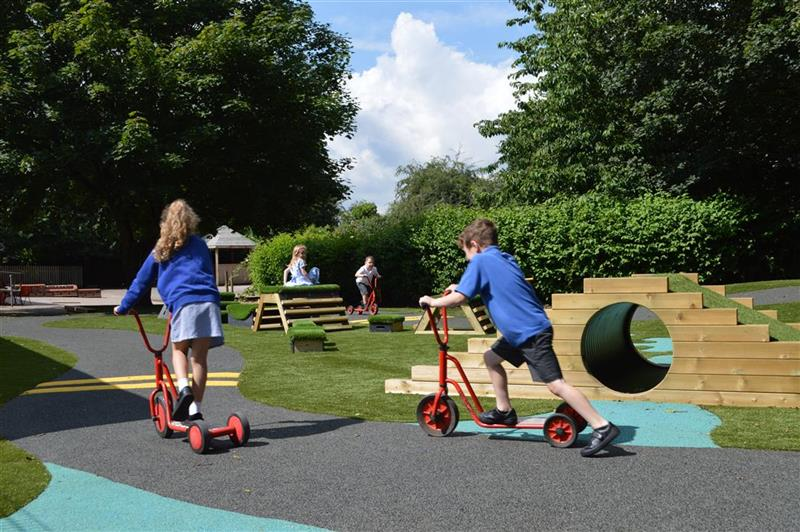 children riding scooters on their new roadway