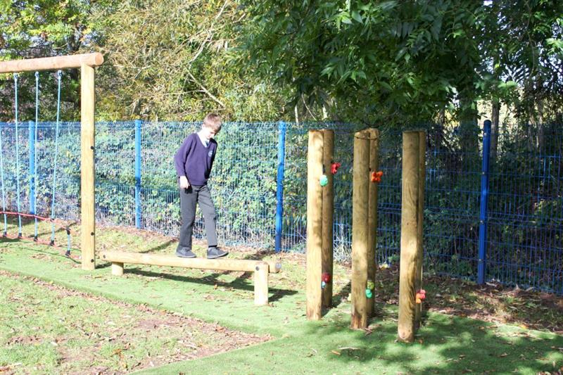 Child balancing on a wooden balance beam installed onto a school field