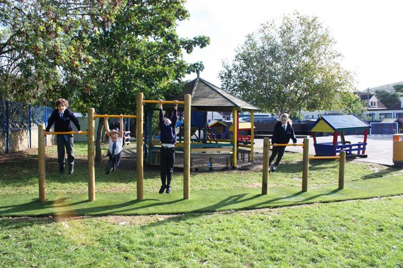 Children hanging on pull up bars on the school playground
