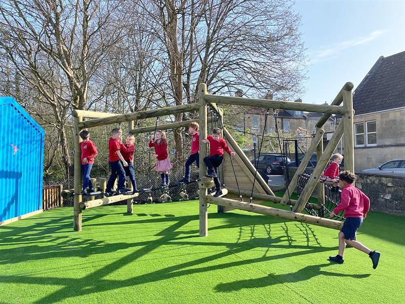10 children playing on Pentagon Play's Puzzlewood Climbing Frame