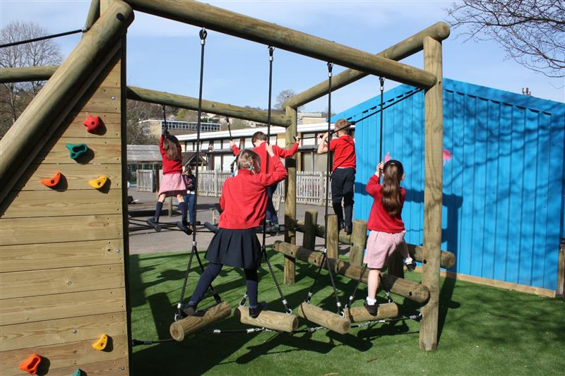 5 children playing on a puzzlewood forest circuit climbing frame