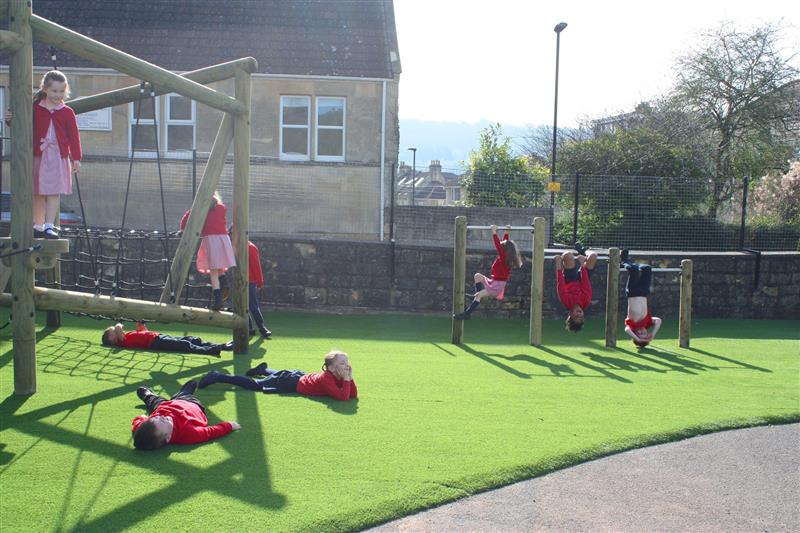 children lying down and resting on artificial grass surfacing
