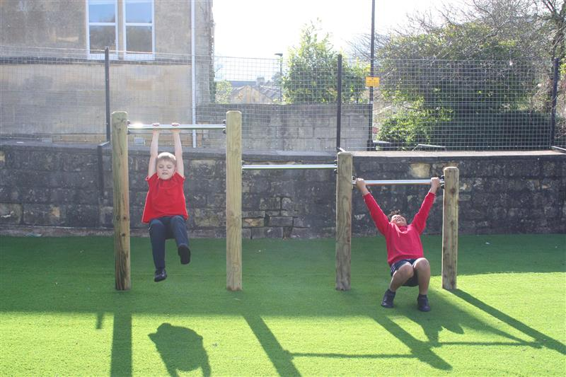2 children swinging from a set of roll over bars installed onto artificial grass