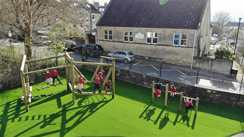 An overhead view of an active play area including a climbing frame and set of roll over bars