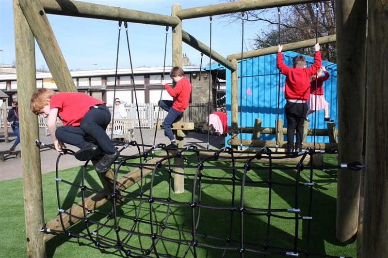 children playing on pentagon play's puzzlewood forest circuit
