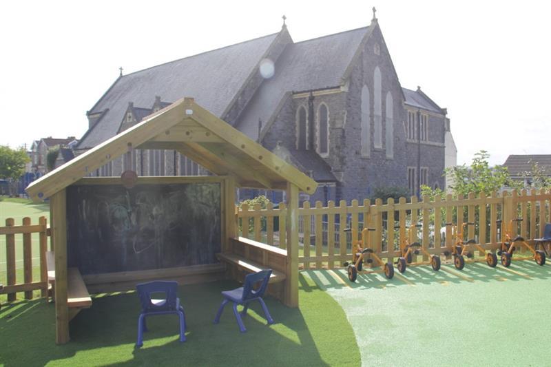 Playhouse installed onto artificial grass playground surfacing