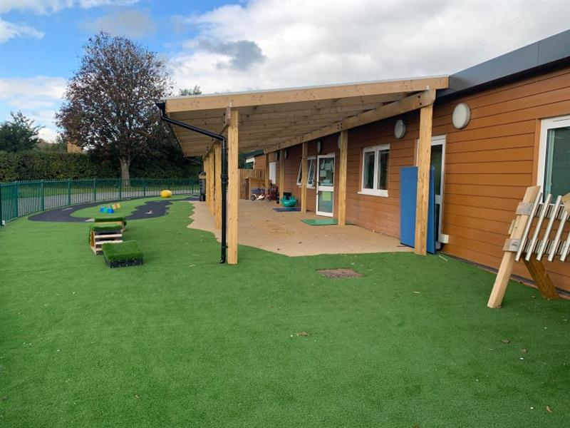 A side view of timber canopy which is attached to school building, with get set go blocks placed onto artificial grass in front of canopy.