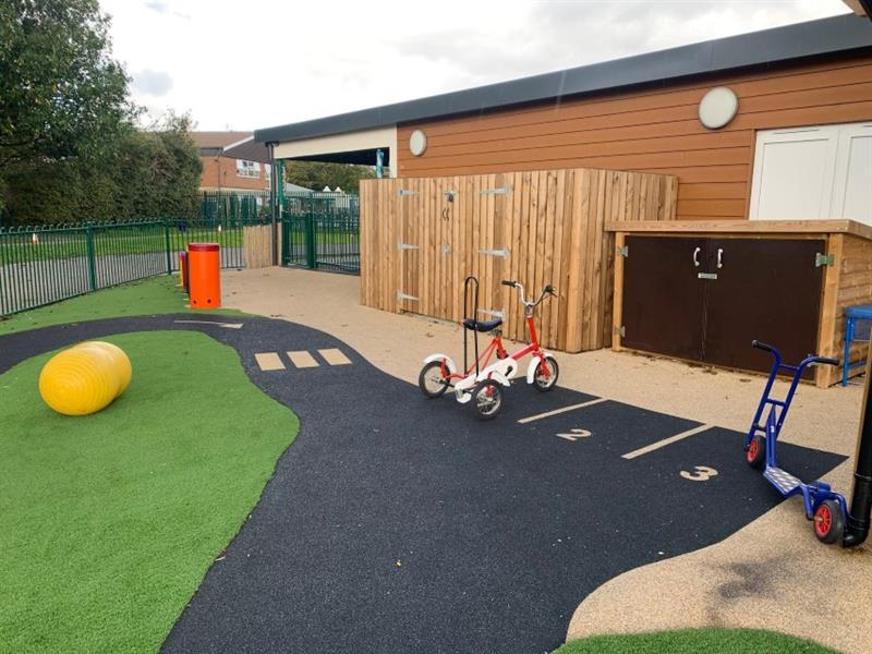 A trike and a scooter parked in parking bays which comes off the roadway using the wetpour surfacing. Installed around artificial grass in front of storage boxes.