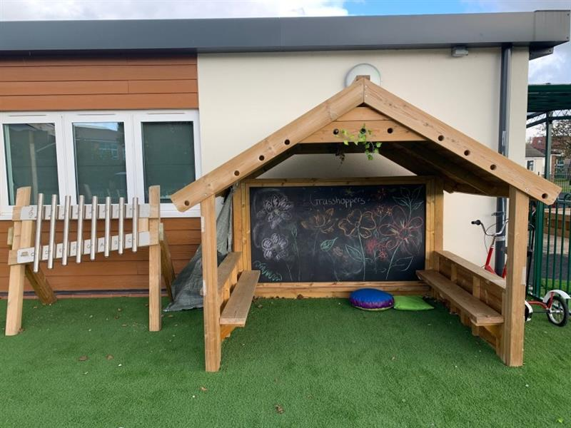 A giant playhouse with walls, benches inside and a chalkboard with drawings of flowers placed in front of school building next to free standing chimes.