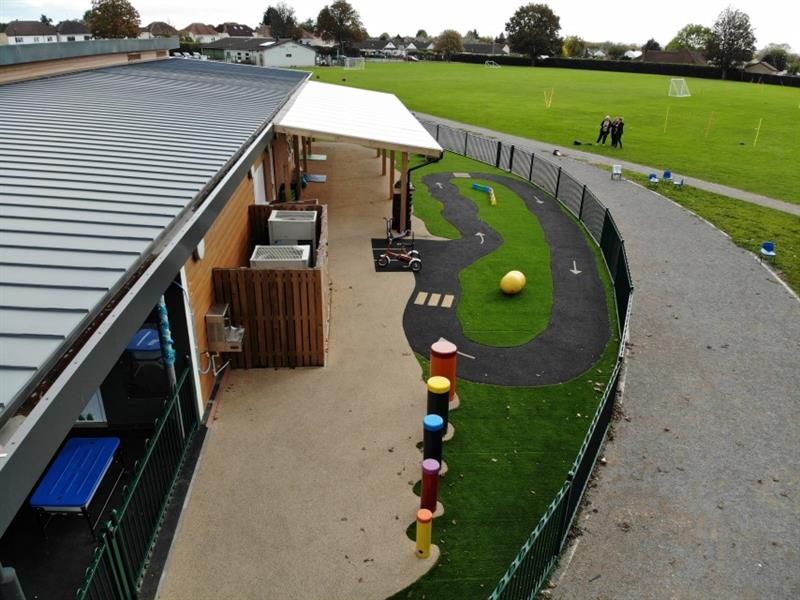 Aerial view of school playground showing African drums, wetpour roadway, and artificial grass with the timber canopy attached to the school building