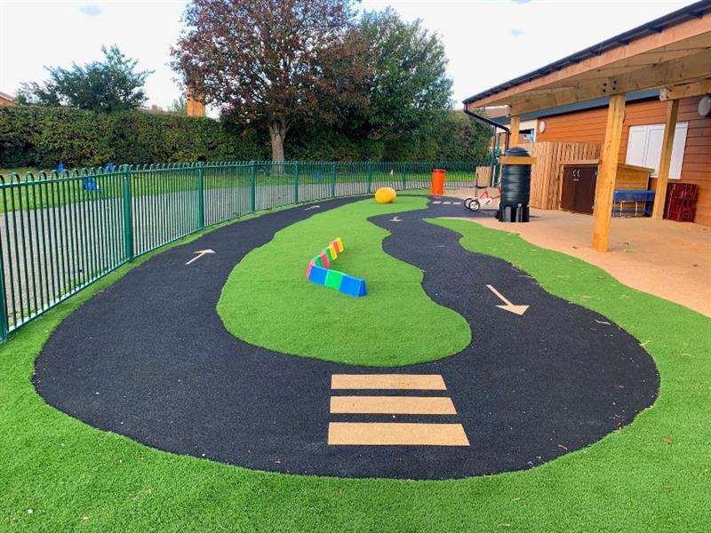 Wetpour roadway with road markings on making a zebra crossing and arrows, surrounded by artificial grass installed in front of the timber canopy.
